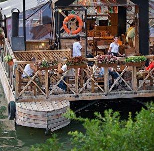 Плавающий ресторан на реке Кура у причала на набережной в грузинской столице