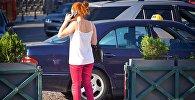 Девушка говорит по мобильному телефону на фоне такси