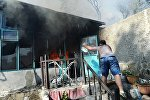 Мужчина тушит пожар в жилом секторе Ростова-на-Дону