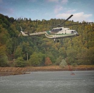 Вертолет Ми-8 МВД Грузии забирает воду в реке для тушения пожара в Боржоми-Харагаульском лесу