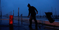 Мусор пролетает мимо человека, который пытается пройти под порывами ветра от урагана Харви в Корпус-Кристи, штат Техас, США