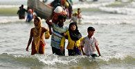 Беженцы из Мьянмы выходят на берег со своими вещами после пересечения границы Бангладеш-Мьянма на лодке через Бенгальский залив