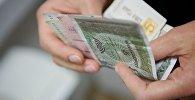Человек держит в руках купюры грузинской валюты лари различного номинала