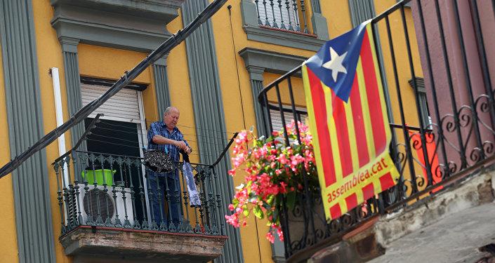 Мужчина развешивает одежду на балконе на севере Барселоны, на фоне флага Каталонии