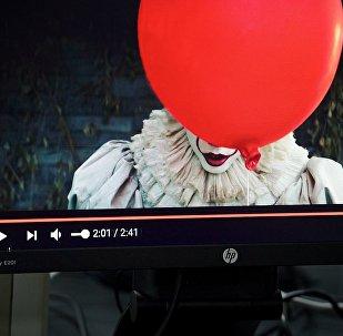 Девушка смотрит трейлер фильма Оно на экране компьютера