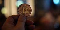 Человек держит в руках сувенирную монету биткоин