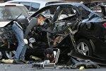 Эксперт рядом с машиной, пострадавшей от взрыва в Киеве