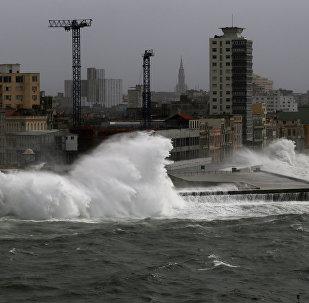 Волны падают на прибрежный бульвар Эль-Малекон