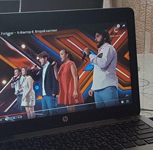 Девушка смотрит выпуск украинского X-Factor с участием грузинской группы Diamonds