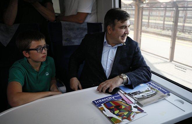 Бывший президент Грузии Михаил Саакашвили и его сын Николоз сидят в поезде на железнодорожной станции в Пшемысле, Польша