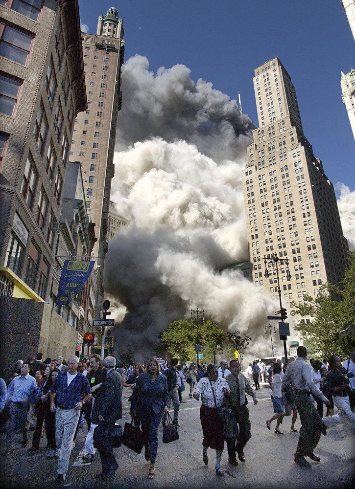 Люди бегут из падающей южной башни Всемирного торгового центра в Нью-Йорке после атаки, совершенной террористами 11 сентября