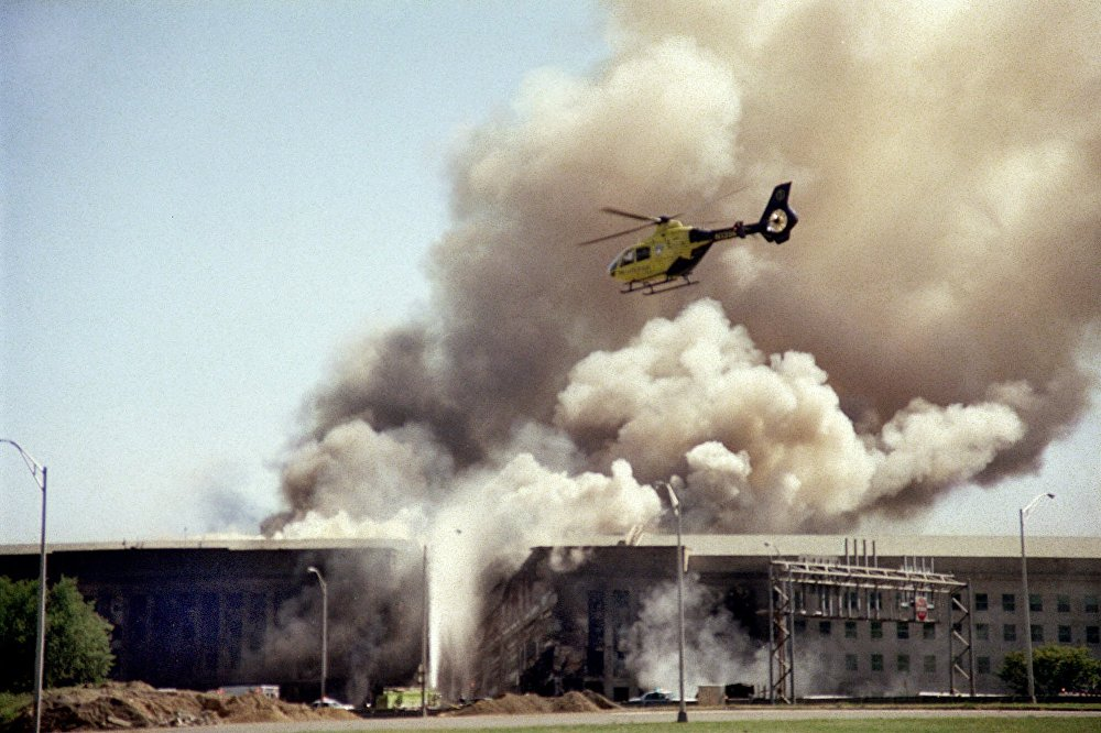 Вертолет пролетает над зданием Пентагона в Вашингтоне после совершенной террористической атаки 11 сентября 2001 года