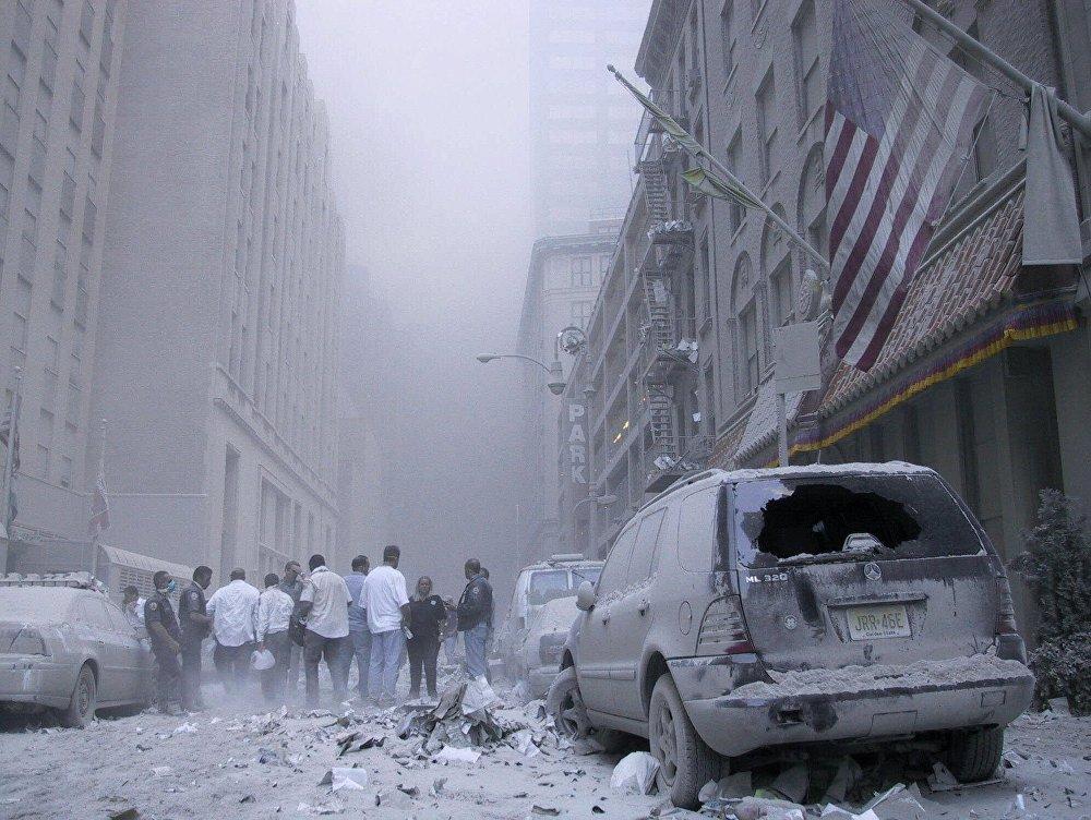 Пыль, мелкие обломки здания и мусор заполняют воздух после падения башен Всемирного торгового центра, атакованного террористами