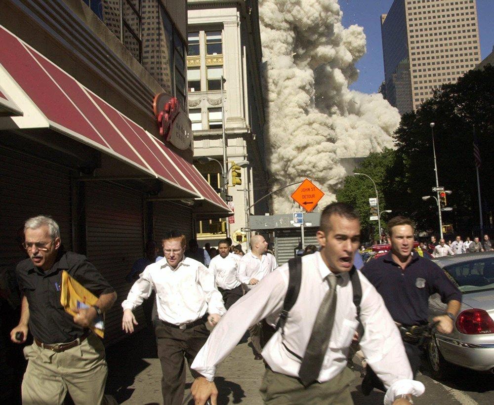 Люди бегут от падающей башни Всемирного торгового центра 11 сентября 2001 года в Нью-Йорке