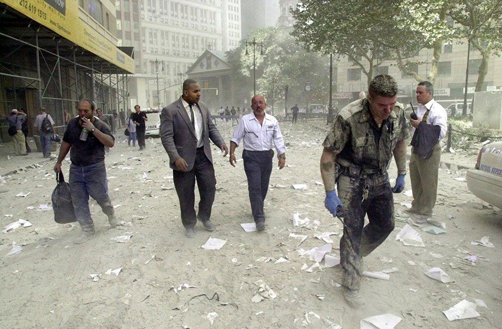 Шокированные люди в сопровождении полицейского бредут по улице, покрытой обломками башен Всемирного торгового центра 11 сентября 2001 года в Нью-Йорке