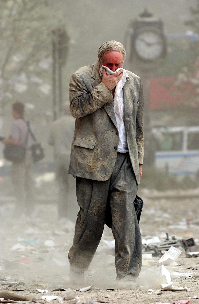 Человек идет через обломки здания после обрушения одной из башен Всемирного торгового центра в Нью-Йорке. Этого человека звали Эдвард Файн - он находился на 78-м этаже первой башни ВТЦ, когда в нее врезался захваченный террористами самолет