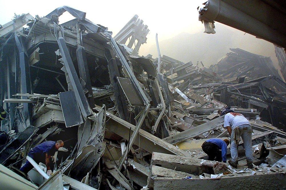 Спасатели в поисках выживших пробираются через обломки башен Всемирного торгового центра 11 сентября 2001 года в Нью-Йорке