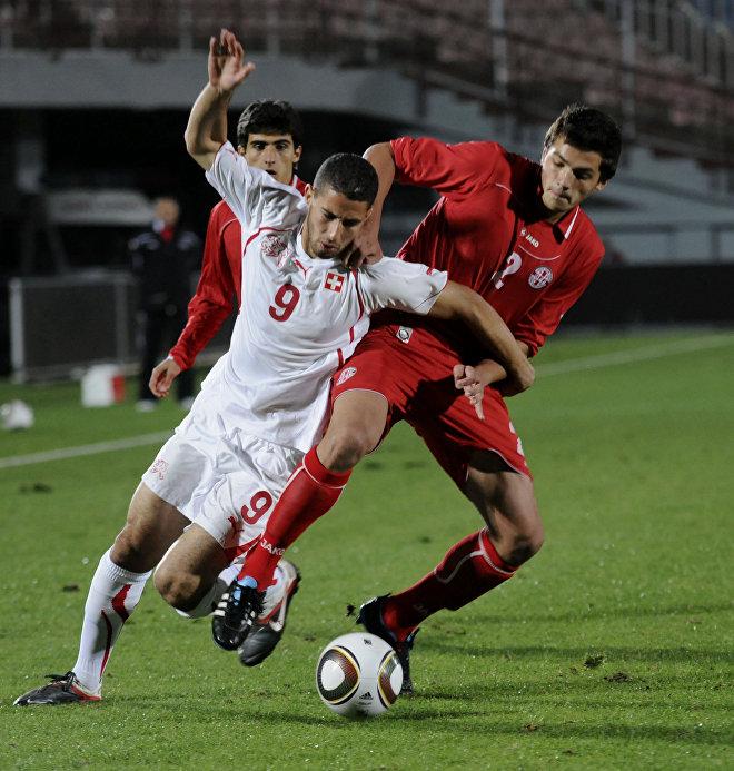 Нассим Бен Халифа (слева) и Давид Хочолава сражаются за мяч во время своей групповой встречи чемпионата Европы по футболу среди юношей до 2013 года в Тбилиси