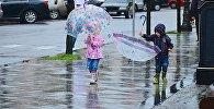 Дети с зонтиками идут по одной из улиц Батуми после дождя