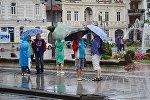 Прохожие с зонтиками идут по одной из улиц Батуми после дождя