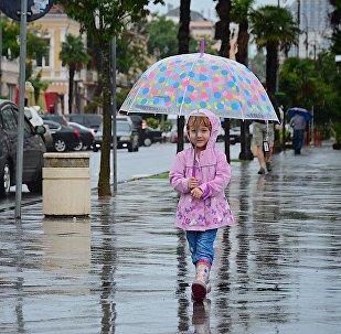 Девочка с зонтиком идет по одной из улиц Батуми после дождя