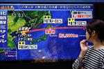 Прохожий смотрит на экран с изображением новости о запуске ракеты Северной Кореей