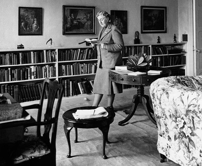 Английская писательница Агата Кристи за чтением книг у себя дома в Девоншире, 1946 год