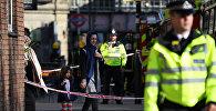 Женщина проходит с ребенком мимо полицейского кордона возле станции Парсонс-Грин в Лондоне, Великобритания