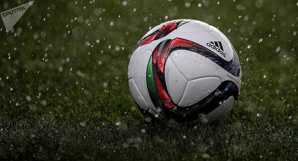 Футбольный мяч на игровом поле под дождем