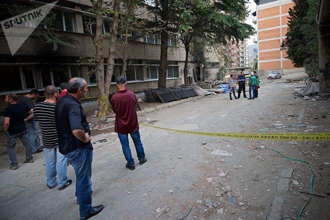 Родственники и близкие погибшего смотрят на место взрыва у бывшего здания Института кибернетики, где работают криминалисты