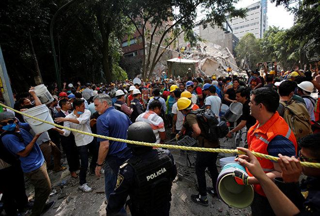 Люди помогают спасателям разбирать завалы и искать выживших после разрушительного землетрясения в Мехико, Мексика