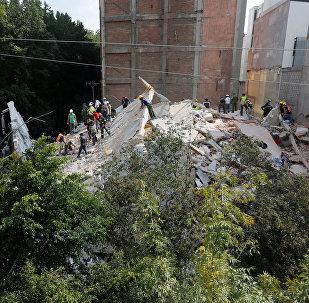 Спасатели работают в поисках выживших на месте разрушенного землетрясением здания в Мехико, Мексика