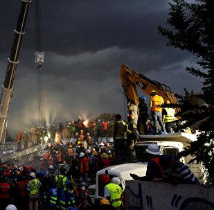 Спасатели и мексиканские солдаты участвуют в спасательной операции в рухнувшем здании после землетрясения в районе Обрера в Мехико, Мексика