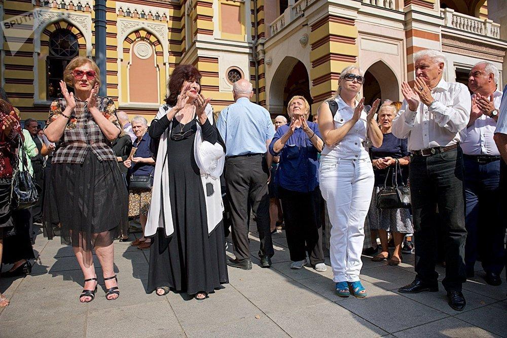 Люди у тбилисского театра оперы и балета аплодисментами провожают траурную процессию, которая несет гроб с телом Зураба Соткилава