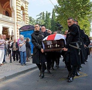 Траурная процессия из грузинских военнослужащих в национальной одежде несет гроб с телом Зураба Соткилава у здания тбилисского театра оперы и балета