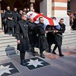Грузинские военнослужащие в национальной одежде выносят гроб с телом Зураба Соткилава из здания тбилисского театра оперы и балета