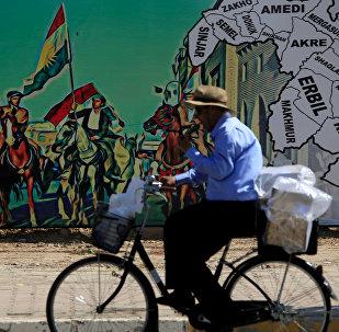 Мужчина едет на велосипеде возле плаката, поддерживающего референдум о независимости Курдистана в Эрбиле, Ирак