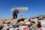 Человек готовится сжечь кучу наркотиков на окраине Джалалабада, Афганистан