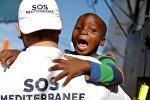 Член экипажа организации SOS Mediterranee с ребенком после спасения группы мигрантов во время операции поиска и спасения (SAR) в Средиземном море от Ливийского побережья