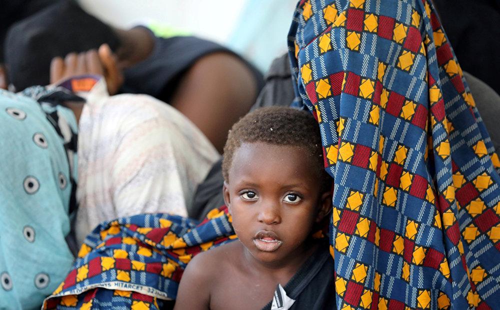 მიგრანტი ბიჭი დედასთან ერთად ზის სამხედრო-საზღვაო ბაზაზე მას შემდეგ, რაც ისინი ლიბიის სანაპირო დაცვამ გადაარჩინა