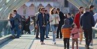Жители и гости грузинской столицы гуляют весенним днем по мосту Мира в центре Тбилиси