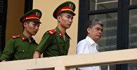 Бывший председатель PetroVietnam Нгуен Суан Шон сопровождается полицией, когда он покидает суд после заседания вердикта в Ханое, Вьетнам
