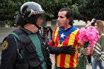Человек, одетый в рубашку с каталонским флагом и держащий гвоздики, сталкивается с испанским офицером гражданской гвардии за пределами избирательного участка для референдума о независимости в Сант-Джулиа-де-Рамис