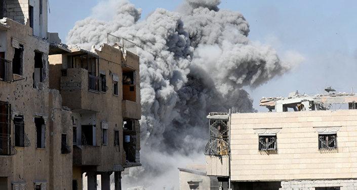 Дым поднимается на позиции боевиков исламского государства после авиационного удара со стороны коалиционных сил возле стадиона в Ракке, Сирия