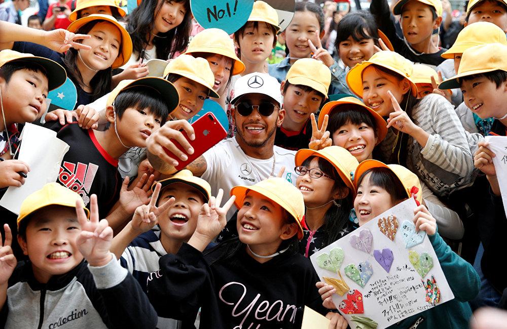 ფორმულა 1-ის Mercedes გუნდის პილოტი ლუის ჰემილტონი სელფის იღებს იაპონელ სკოლის მოსწავლეებთან