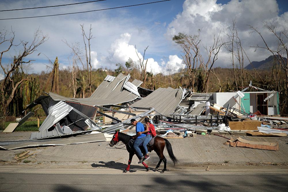 ადგილობრივები ცხენებით მიდიან ქარიშხალი მარიას შედეგად დანგრეულ შენობებთან, პუერტო-რიკო