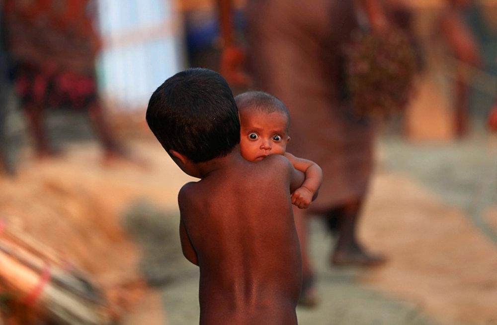 ბიჭს პატარა ბავშვი მიჰყავს დევნილთა ბანაკში, ბანგლადეში