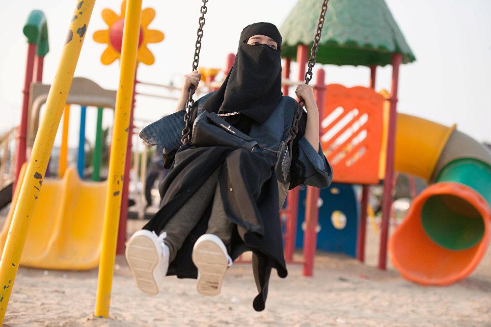 ქალი პარკში საქანელაში ზის, საუდის არაბეთი