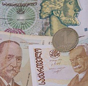 Монета достоинством в 1 лари на банковских купюрах различного номинала