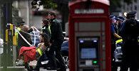 Скорая помощь оказывает помощь женщине возле Музея естественной истории, после того как автомобиль заехал на тротуар в Лондоне, Великобритания